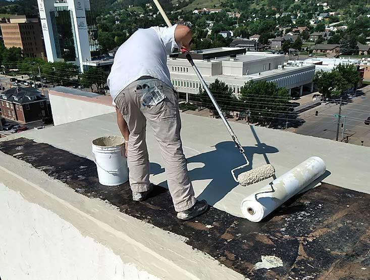 Raintite crew member spreading roof protectant