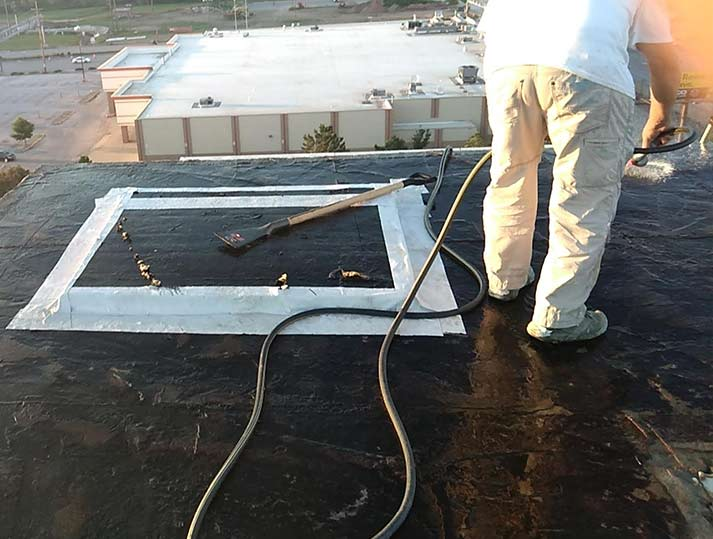 Raintite crewmember on black commercial roof